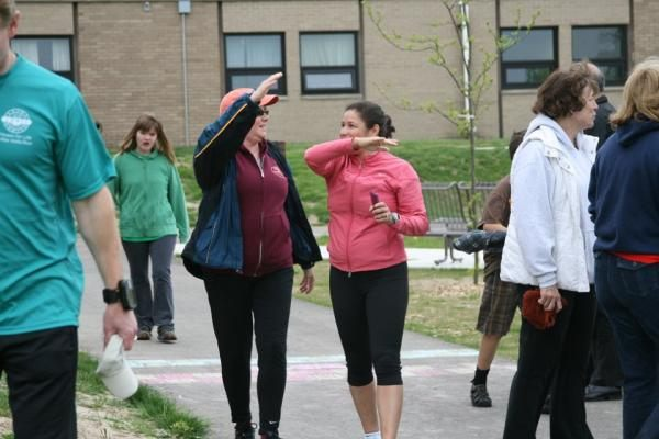 Two female runners in exercise clothes give a high five after they cross the finsih line on the St. Louis Center Special needs playground.